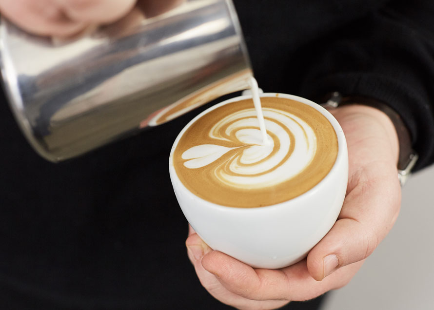 Finishing a tulip latte art design in white ceramic cup