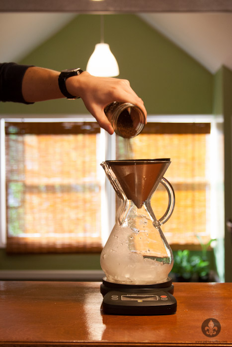 puring coffee grounds into chemex