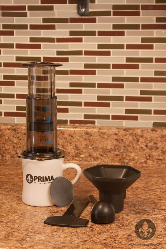 Aeropress Coffee Maker with accessories and a Prima Coffee diner mug