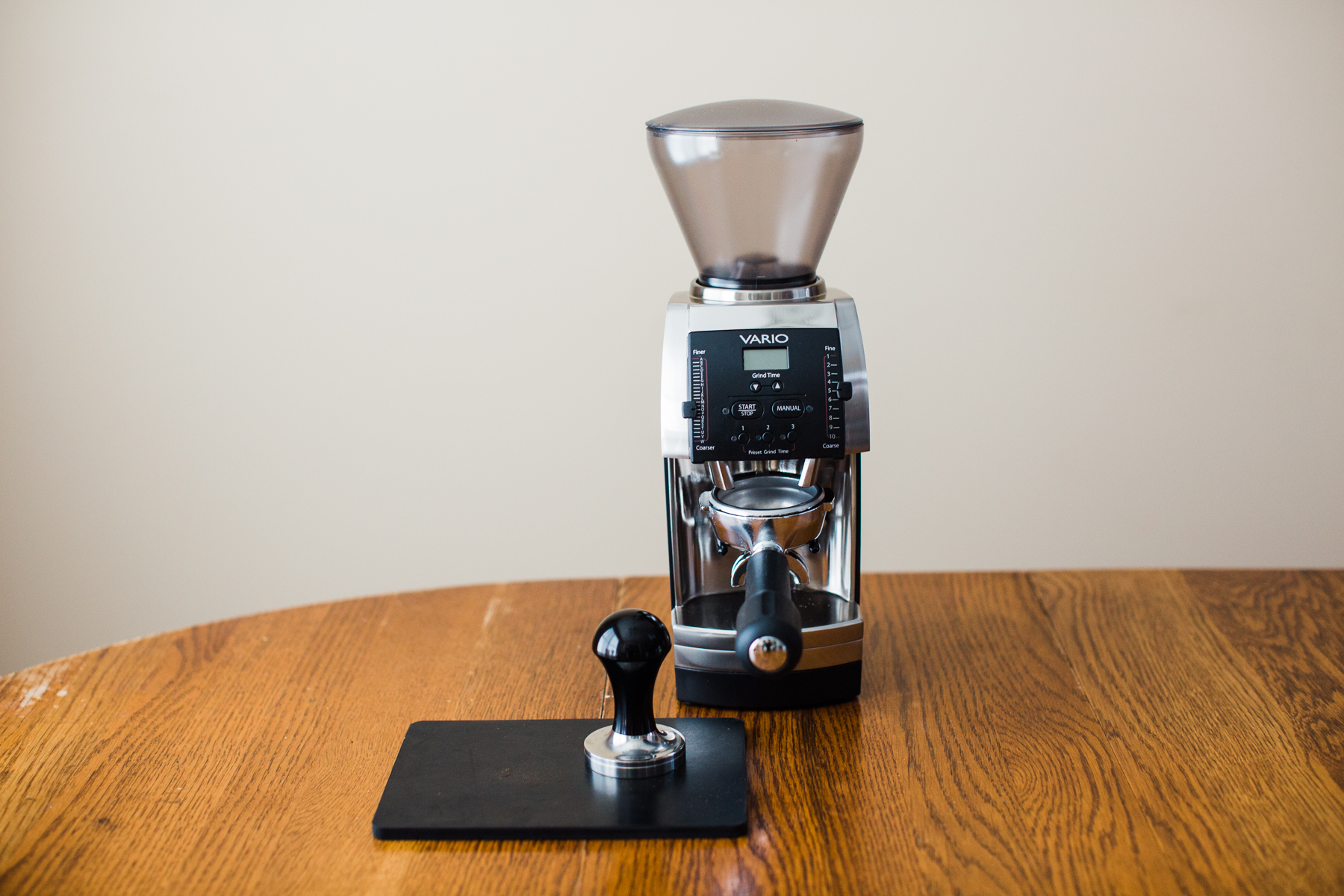 A Baratza Vario holding a portafilter on top of a table with other espresso brewing equipment.