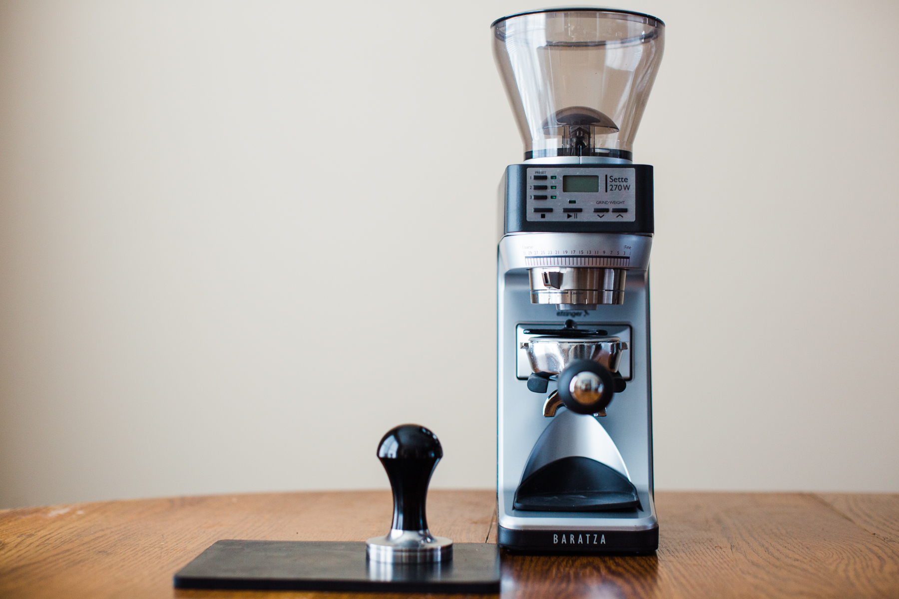 A Baratza Sette 270W holding a portafilter on top of a table with other espresso brewing equipment.