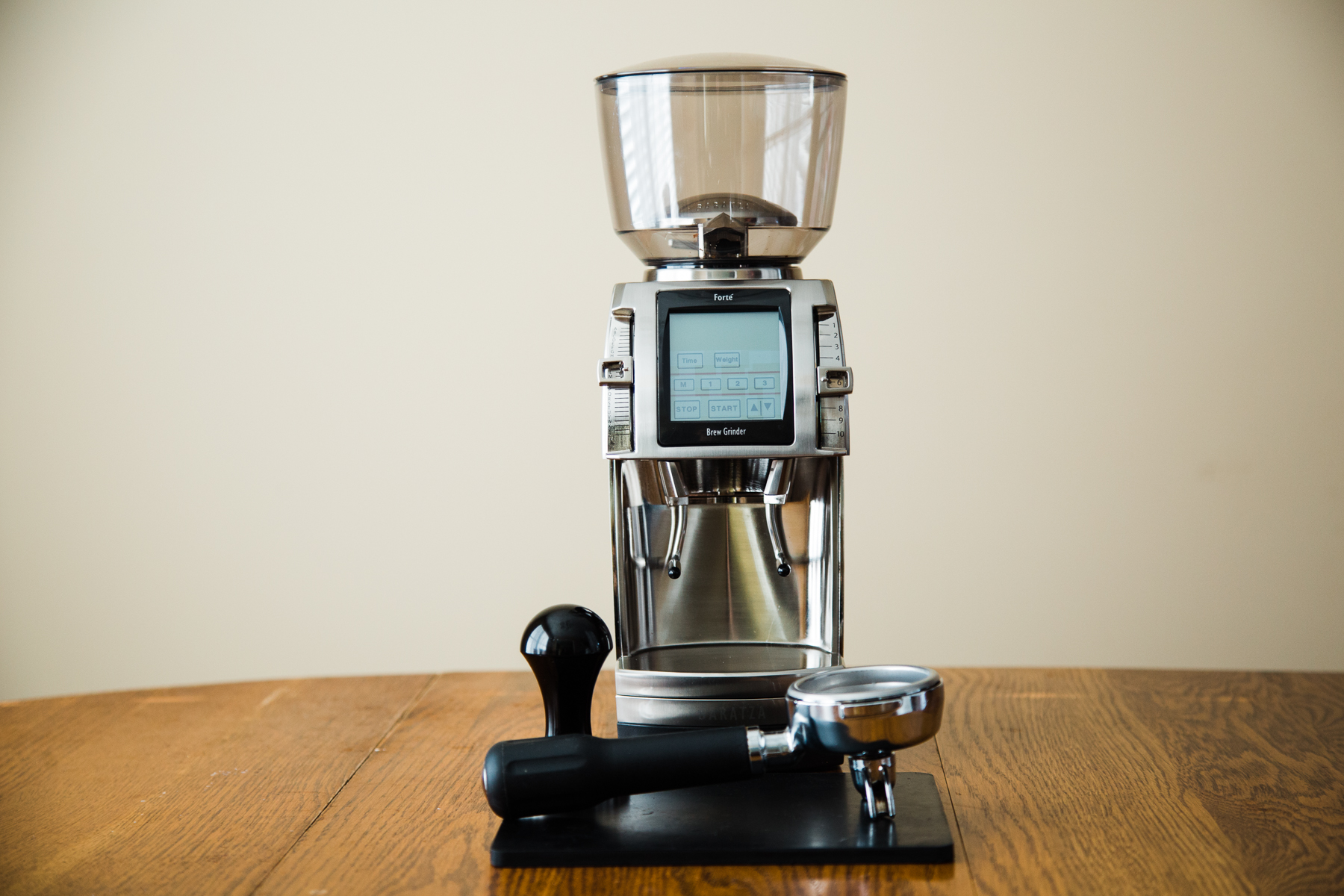 A Baratza Forte on a table with various espresso brewing equipment.