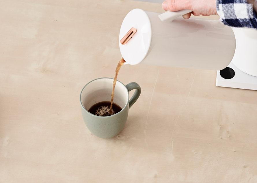 Decanting french press coffee into a coffee mug