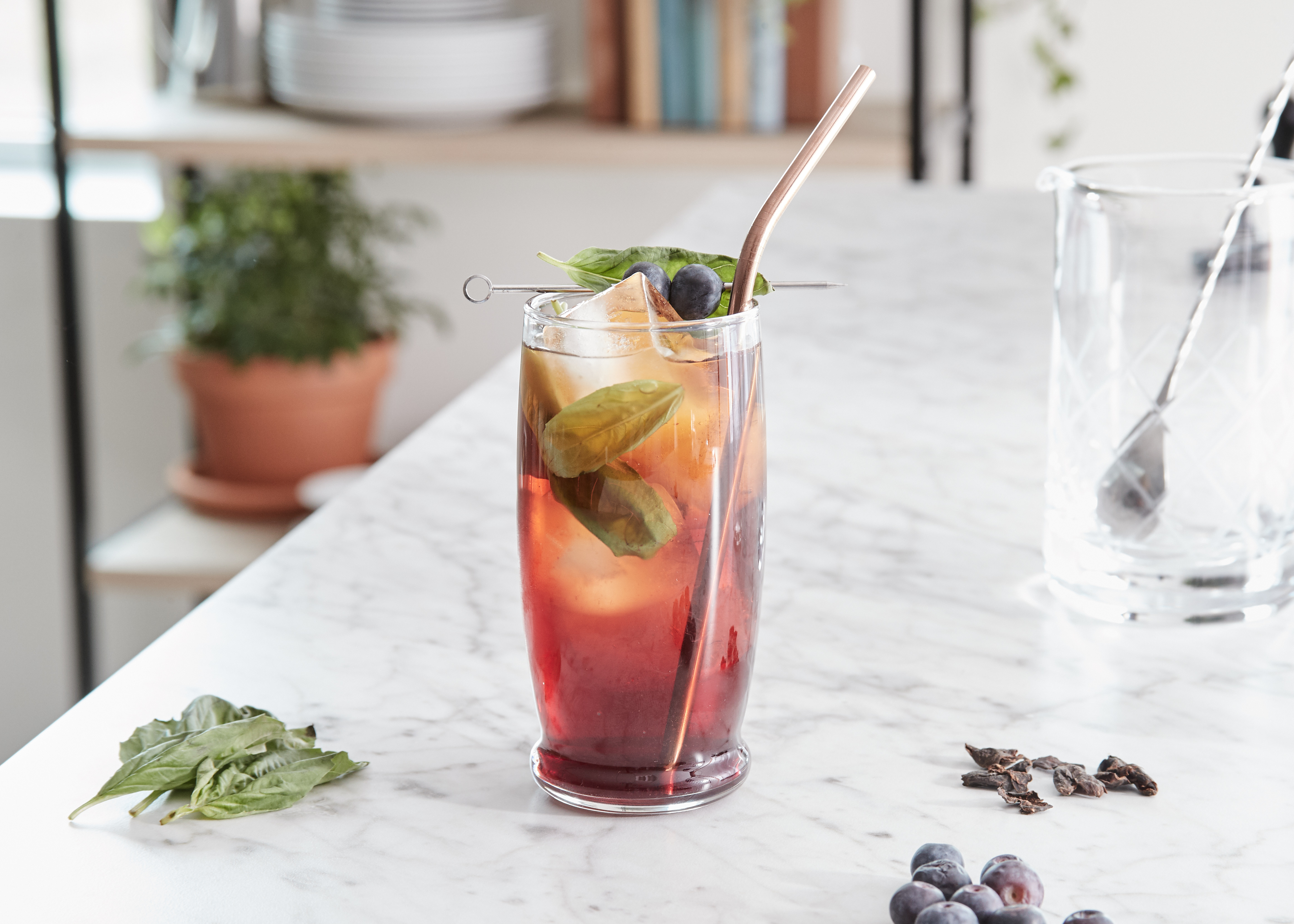 Blueberry + Basil Cascara Sweet Tea served with a straw and ingredients on the table