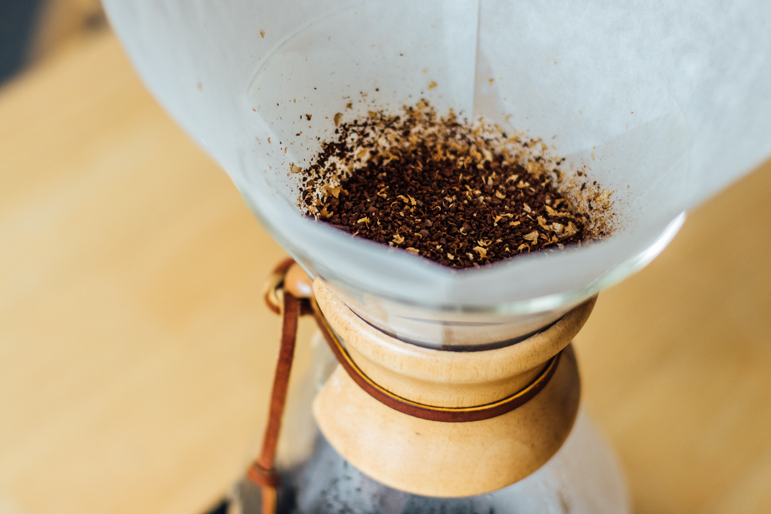 Close up of a wooden neck Chemex with dry grounds inside the wet filter.
