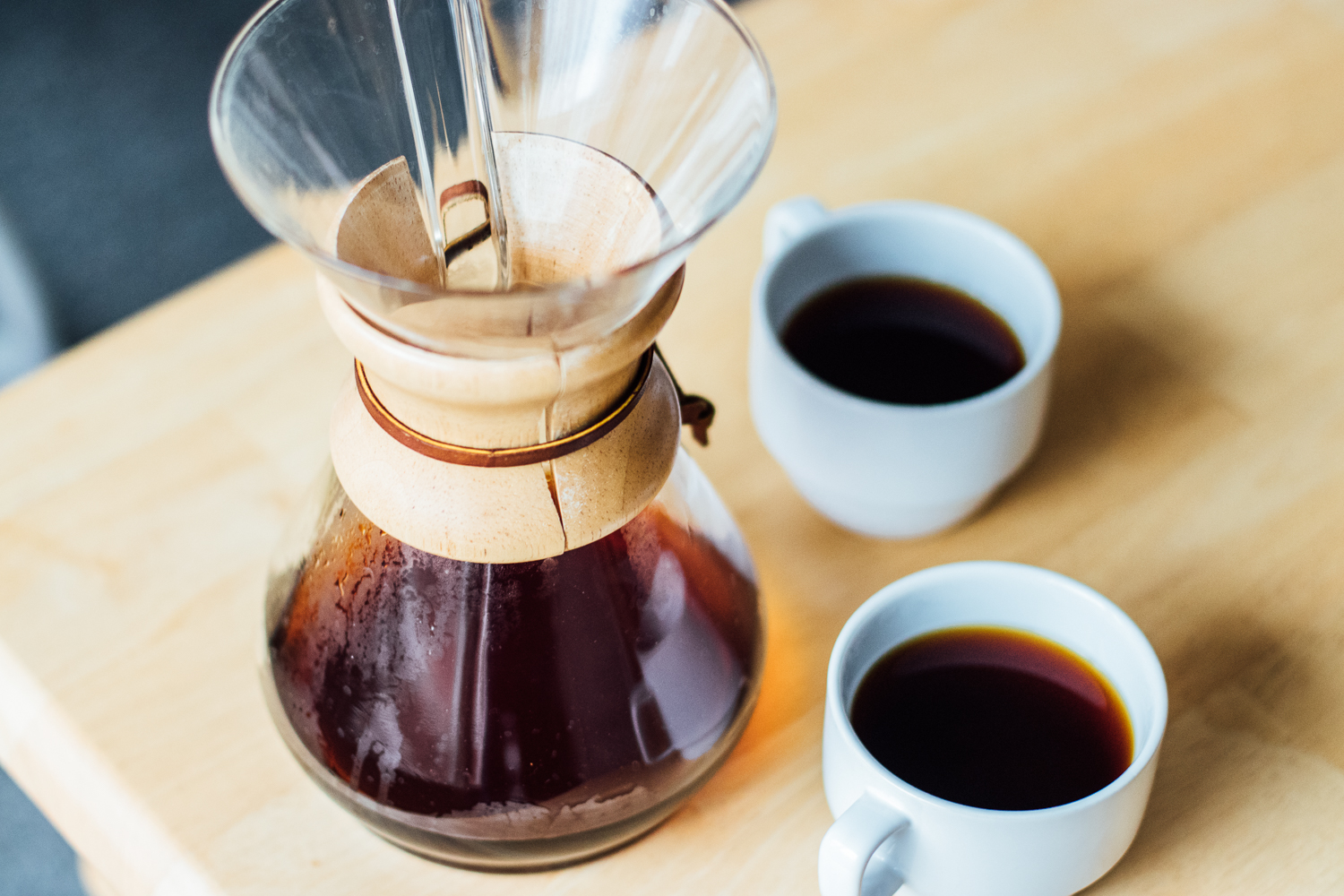 A closeup of the wooden neck Chemex with coffee inside it, alongside two white mugs full of coffee.