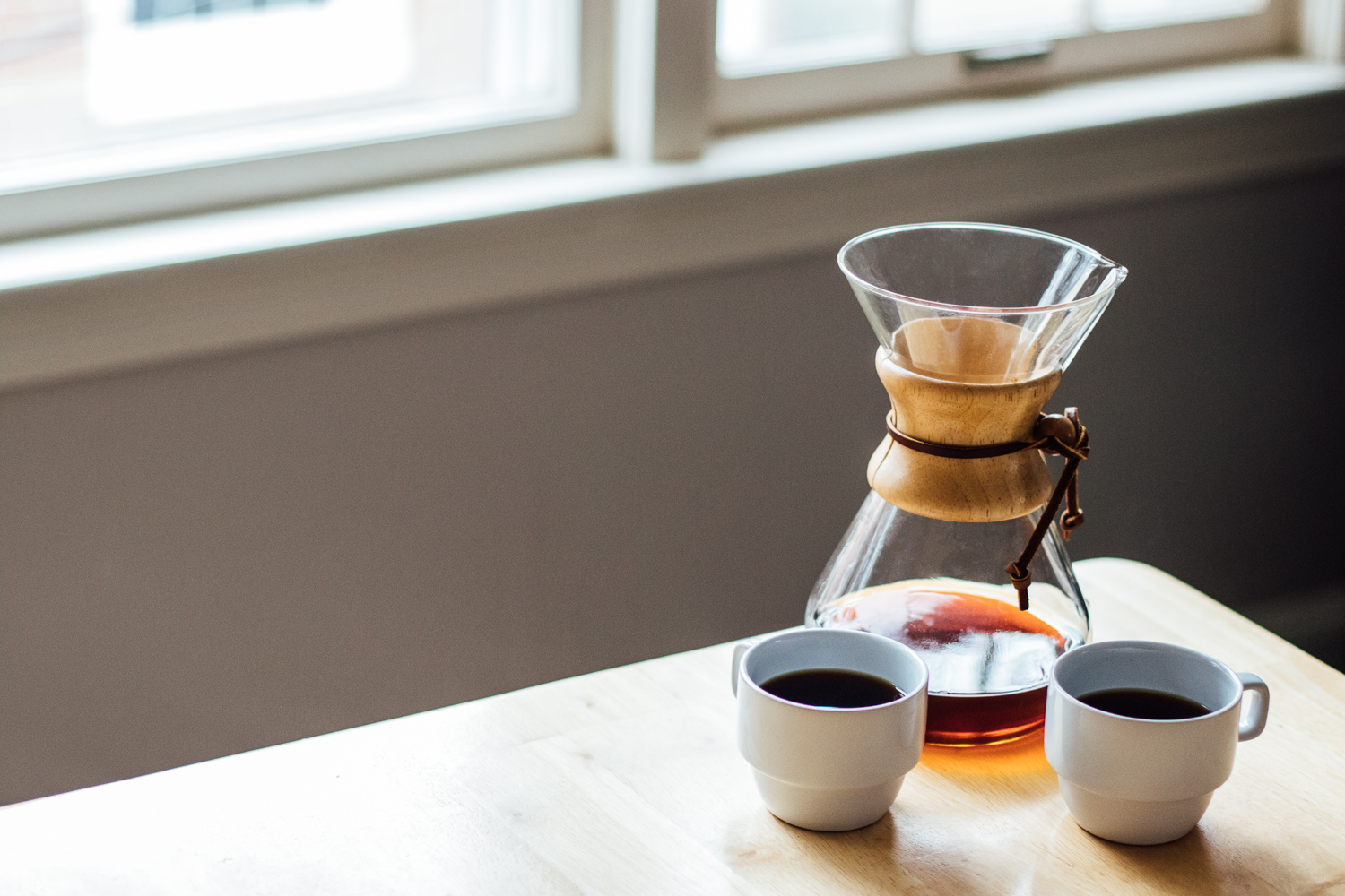 Chemex and two mugs of coffee on a table by a window.