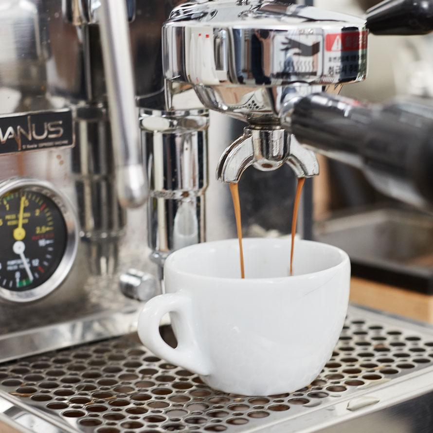 Espresso brewing into a white ceramic cup