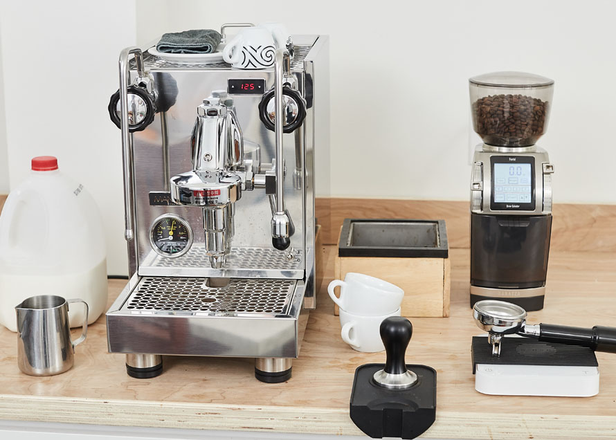 Milk, steaming pitcher, espresso machine, cups, knockbox, tamper, tamp mat, scale, and coffee grinder