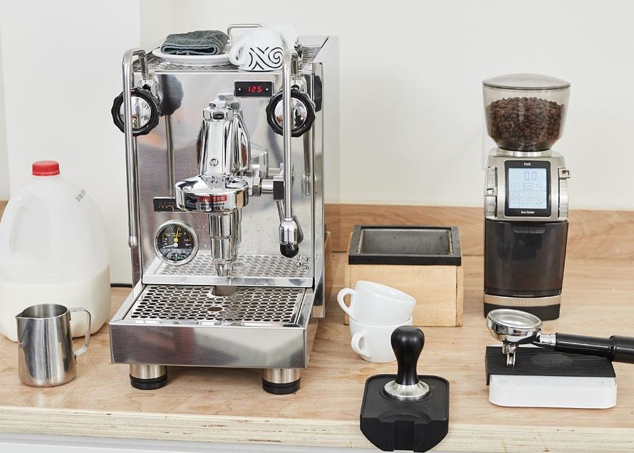 Milk, steaming pitcher, espresso machine, cups, knockbox, tamper, tamp mat, scale, and coffee grinder