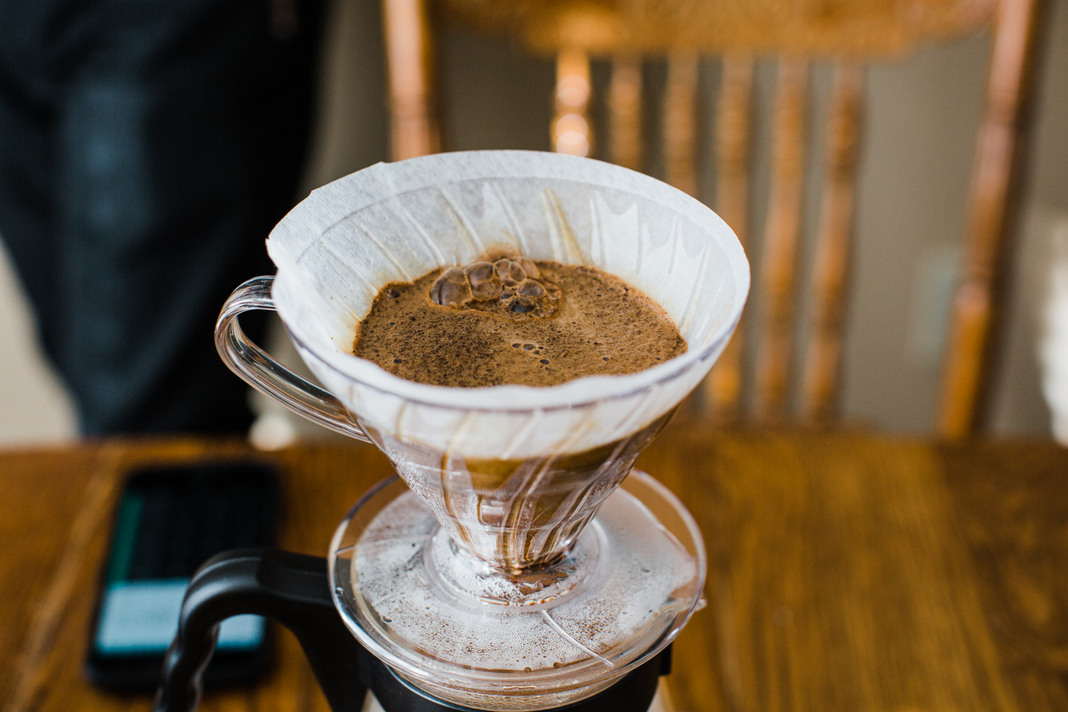 A plastic Hario V60 with coffee blooming inside one of Hario's new tabbed filters. The V60 is sitting on top of a size 03 Hario carafe on top of a wooden table with a wooden chair behind it.