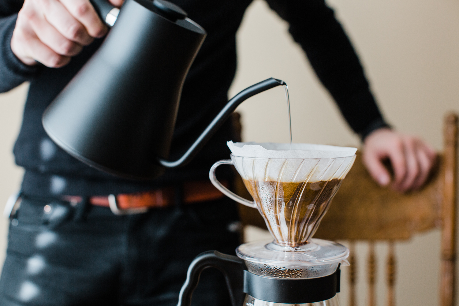 A person brewing coffee with a plastic, size 2 V60, using a tabbed filter, as well as a size 03 glass Hario carafe and a matte black Fellow Stagg.