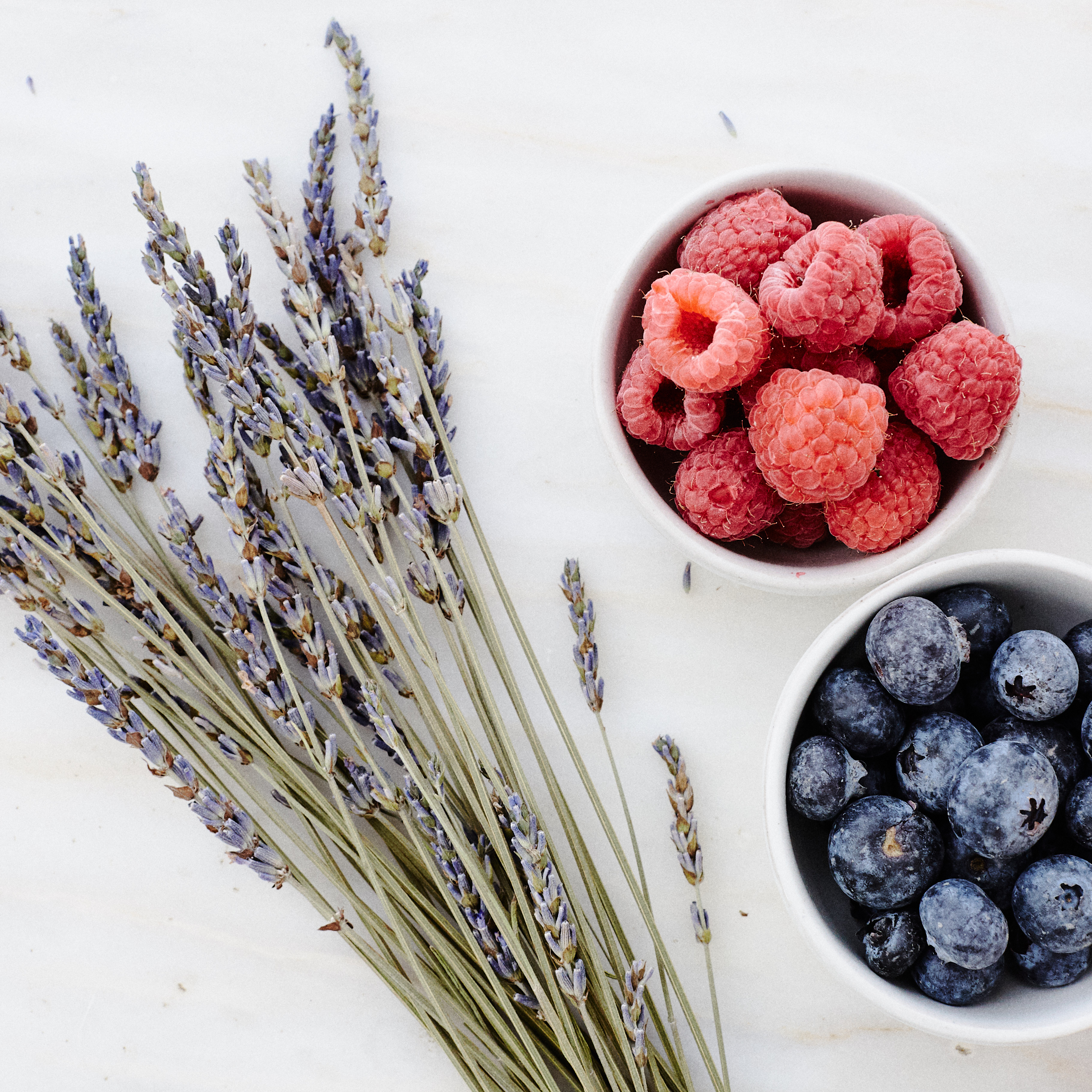 Bowls of raspberries and bluberries with lavender plant