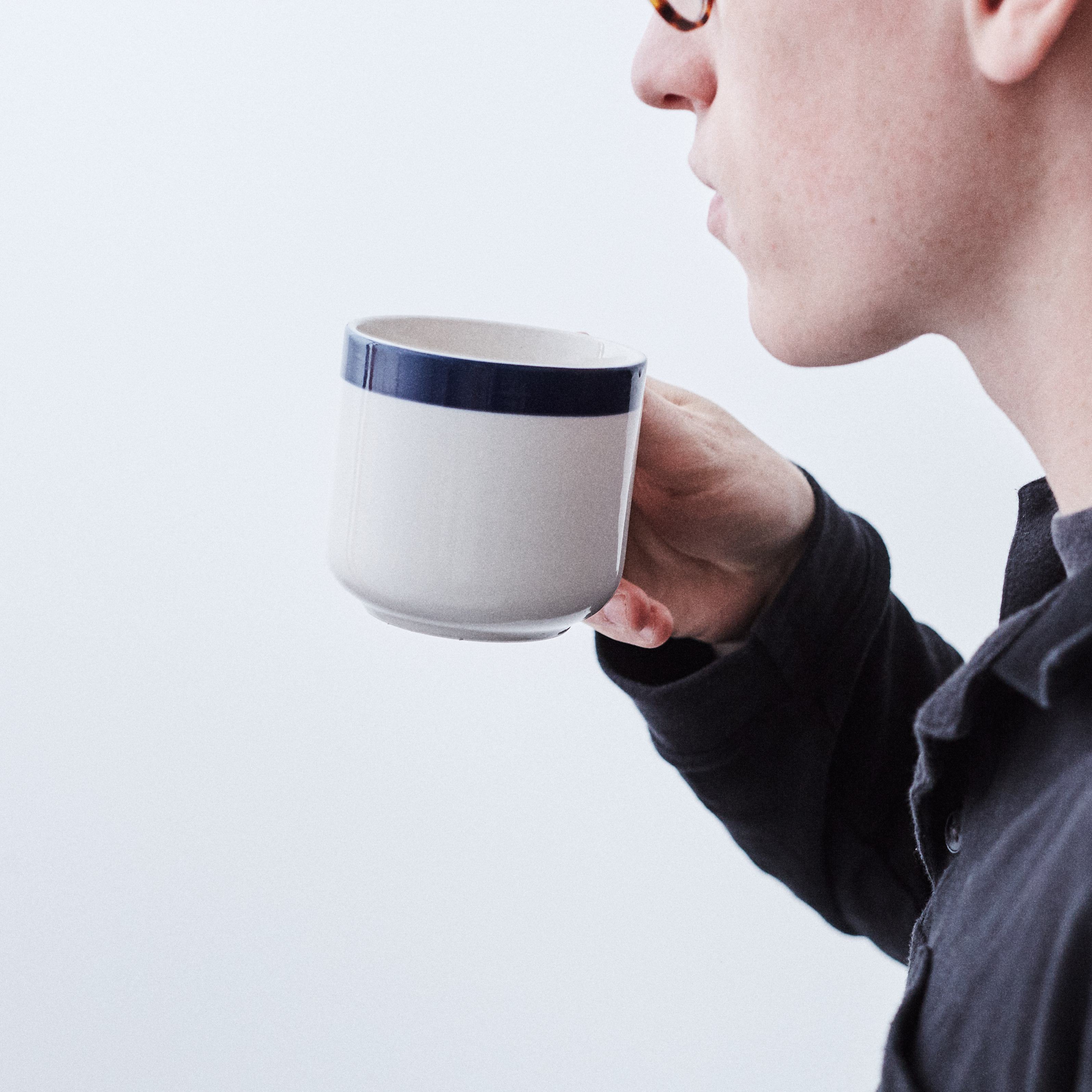 Person sipping coffee from a white mug with blue rim
