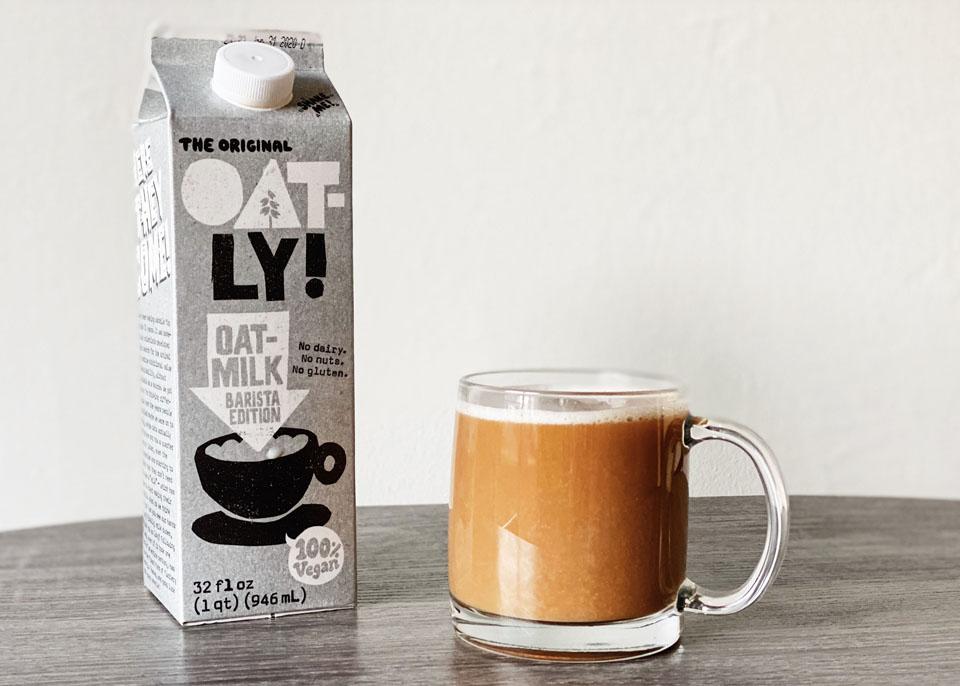 Carton of Oatly next to a mug of milky coffee