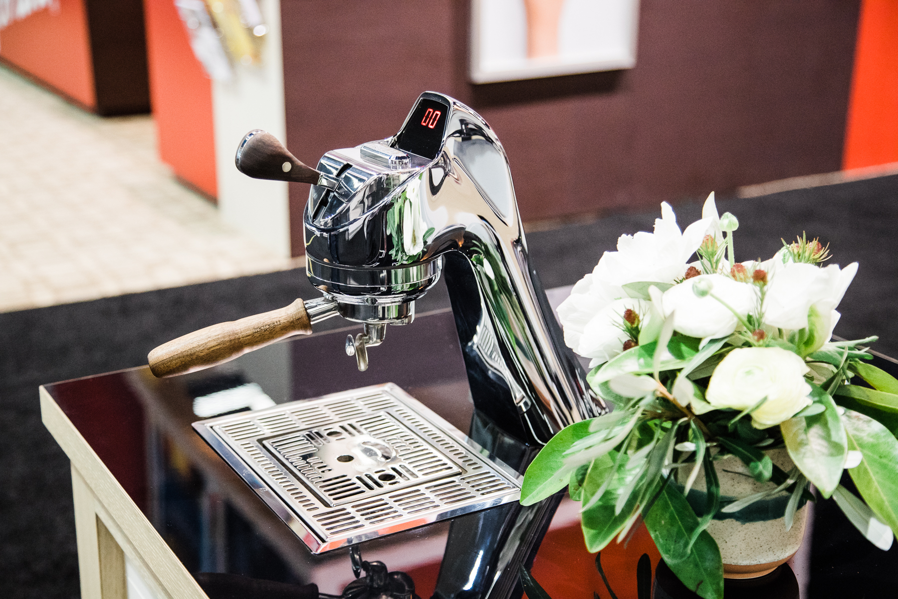 The neck and group head of the Modbar Espresso AV next to a plant on a counter top at the 2018 Coffee Expo.