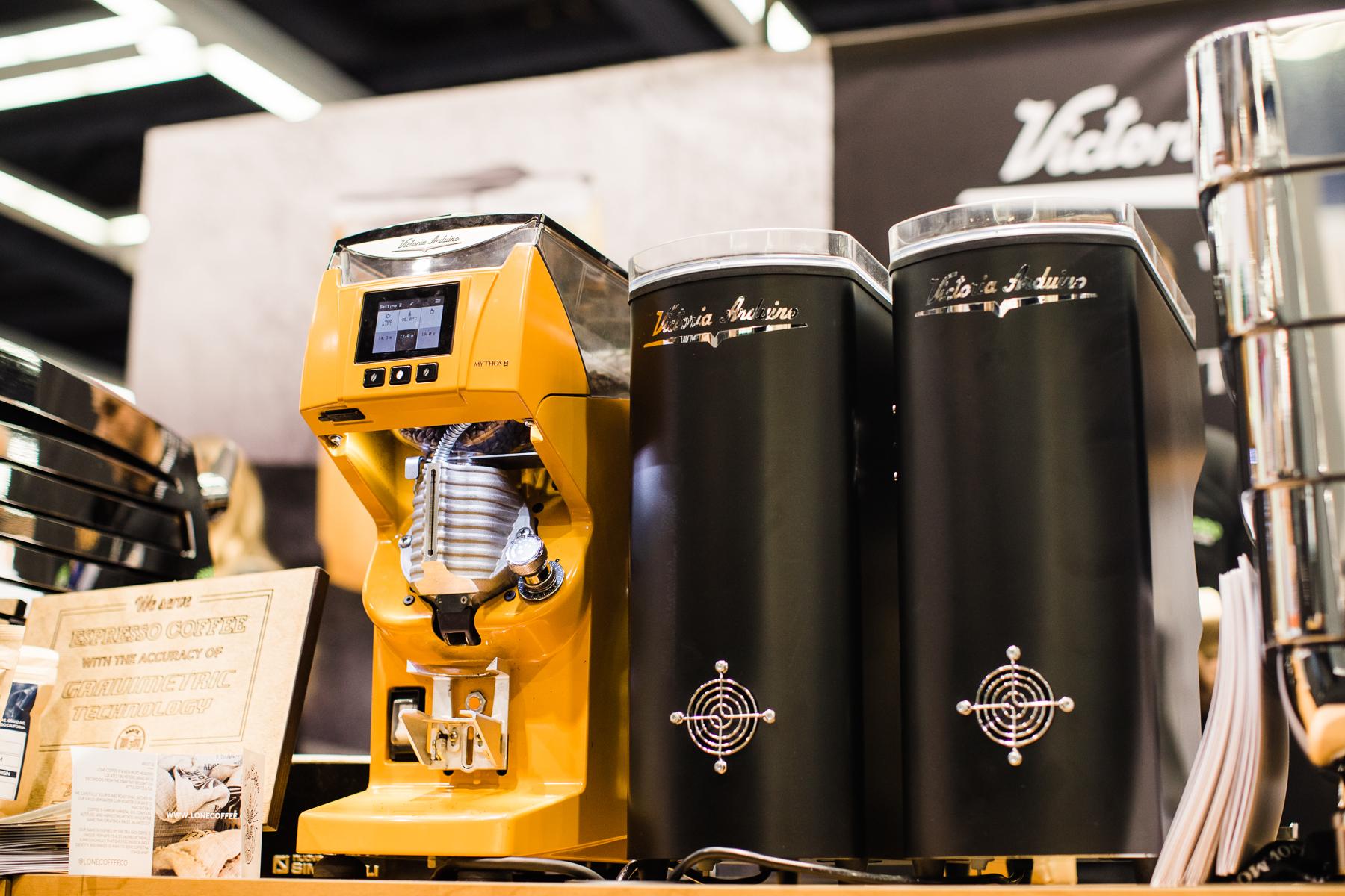 The Yellow Nuova Simonelli Victoria Arduino Mythos 2 next to two Mythos 1s at the 2018 Coffee Expo.