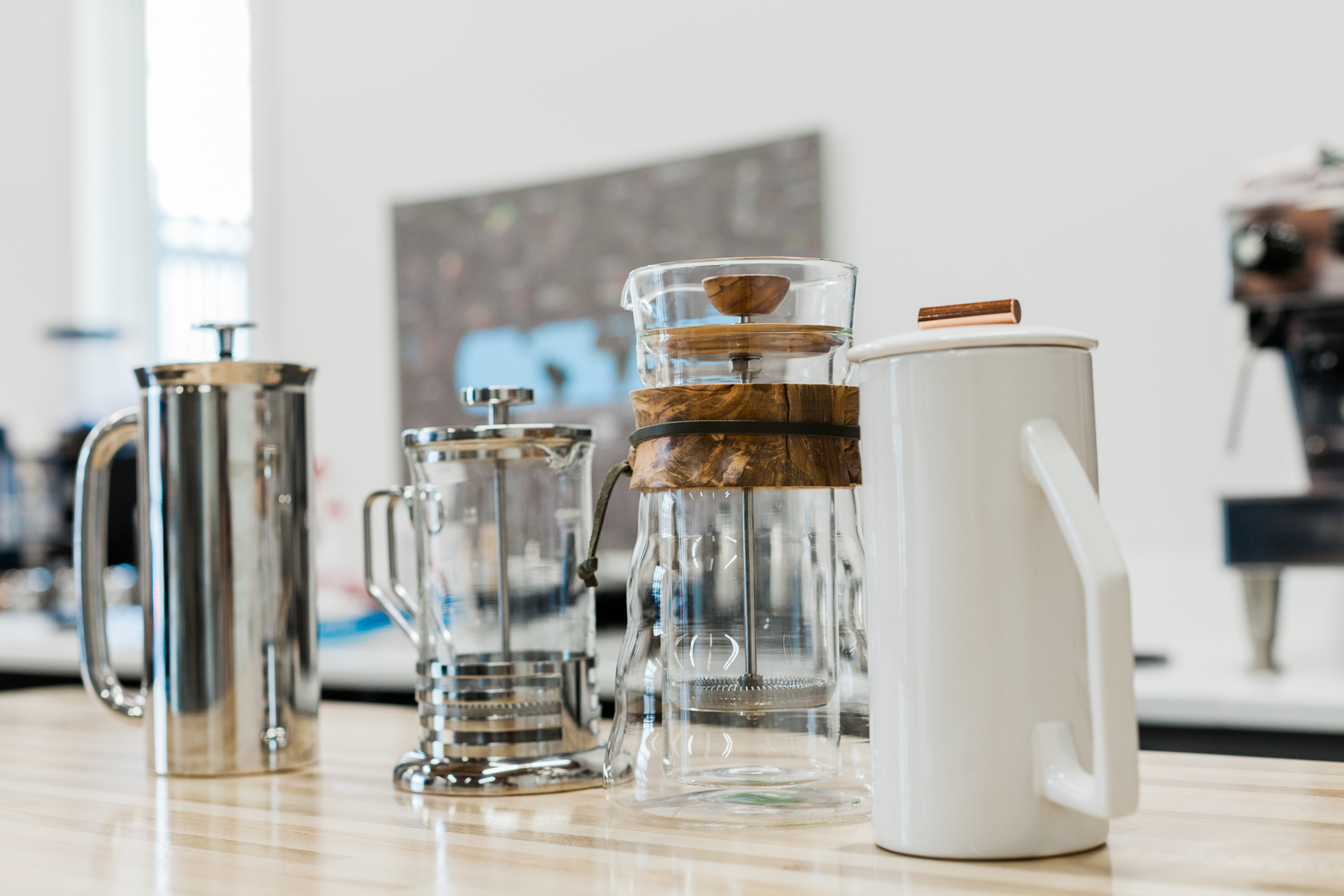 A double-walled stainless steel Espro press, a single-walled glass Hario French press, a double-walled glass Hario French press, and a single-walled white ceramic Yield Design French press.