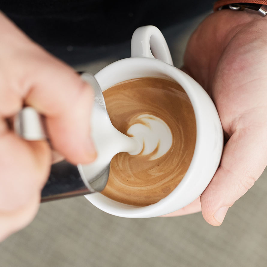 Pouring milk close to the surface of the coffee to start making white shapes