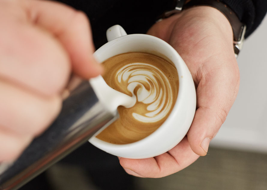 Stacks of latte art wiggles in a white cup