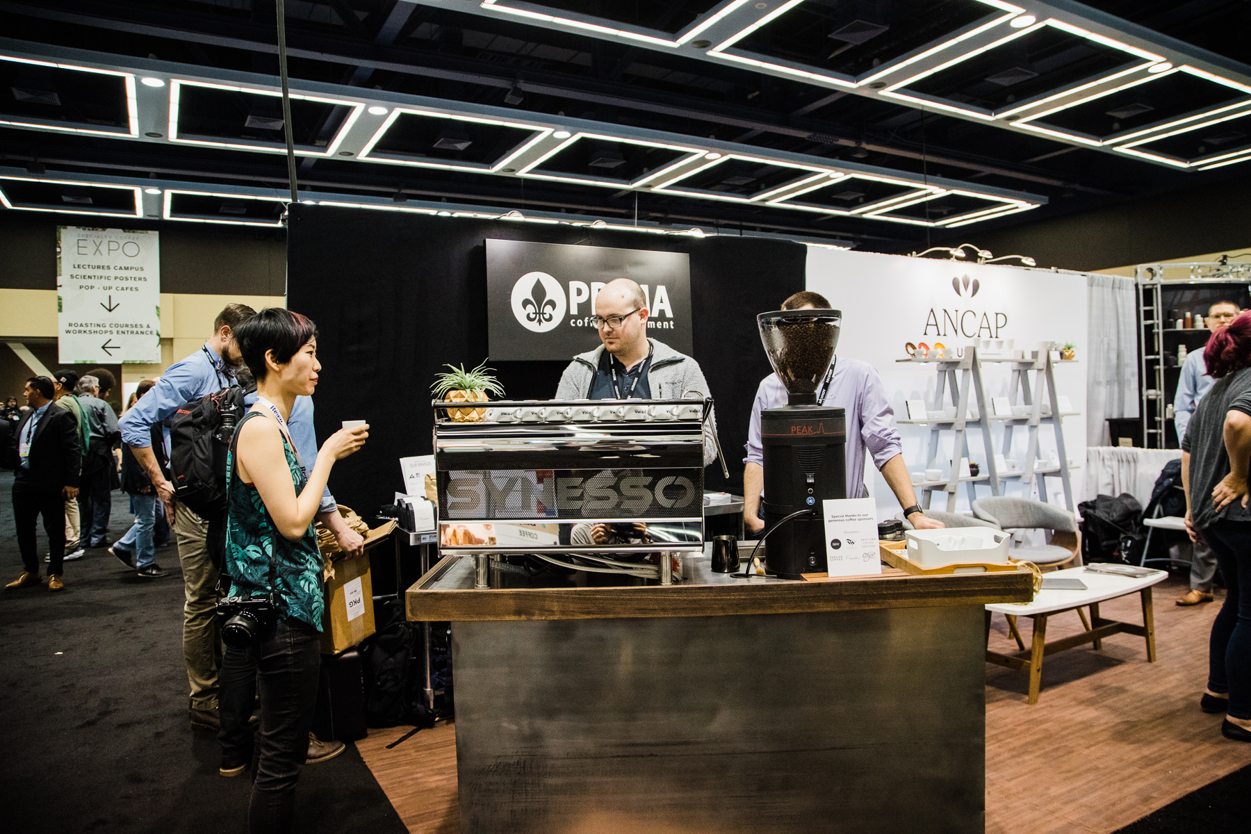 A Synesso M V P Hydra, a Mahlkonig Peak,and a Puqpress on a coffee brew cart with people drinking coffee in the Prima Coffee booth at the 2018 Coffee Expo.