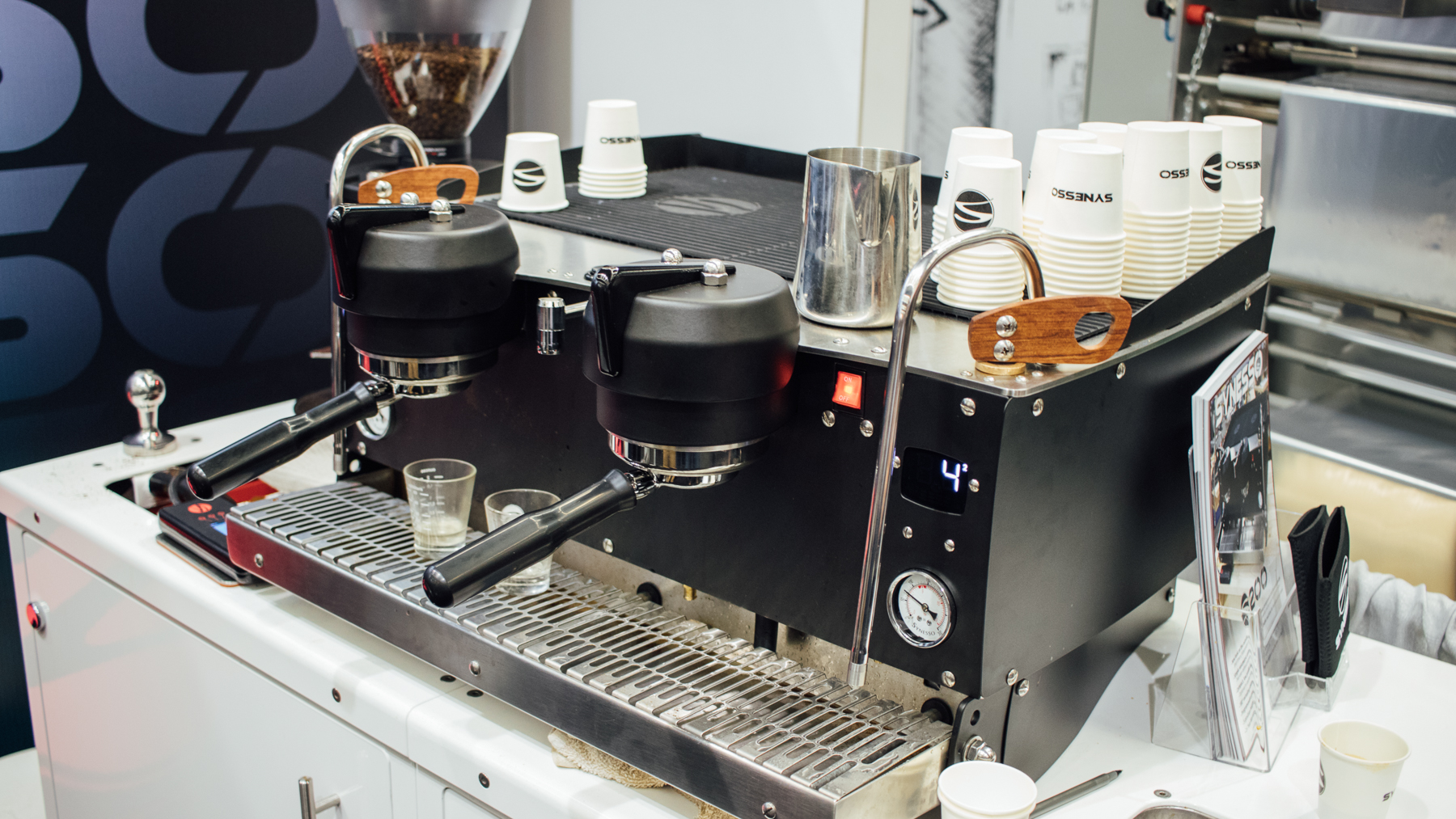 A black Synesso S 200 on a white cabinet at the 2018 Coffee Expo.
