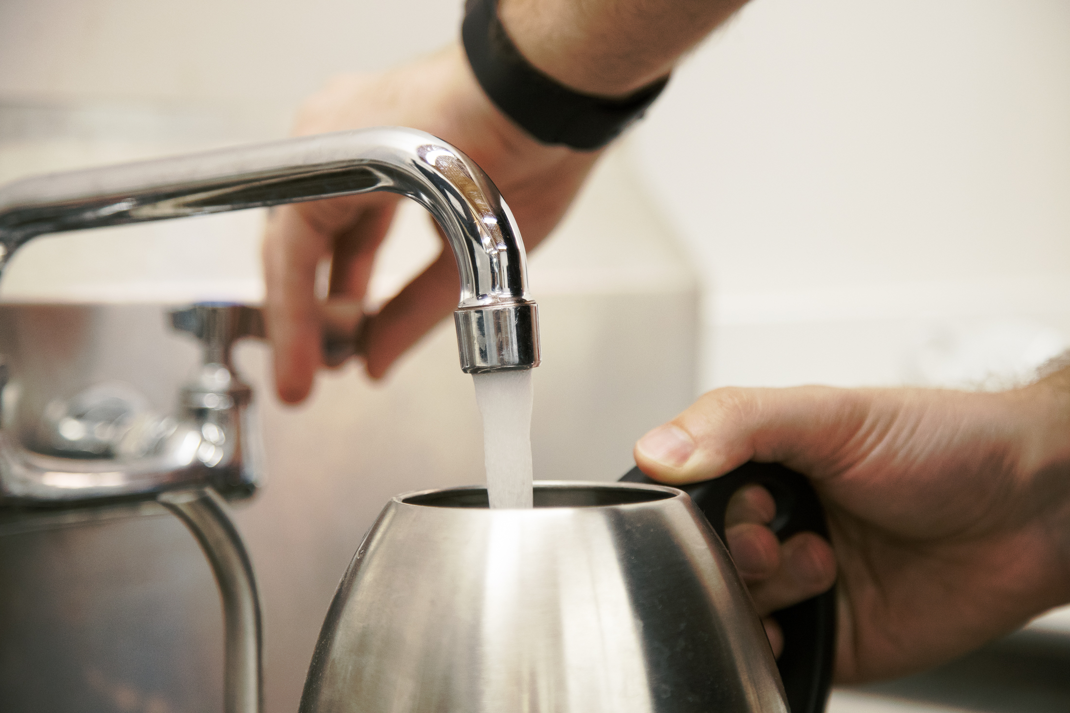 Water coming out of a faucet into a gooseneck kettle.