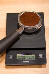 Portafilter with ground coffee on a scale.