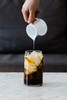 Pouring cream into a Libbey Can Shaped Glass with cold brew and ice in it.