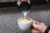 Pouring latte art with a Barista Hustle Precision Milk Pitcher into a Ancap mug.