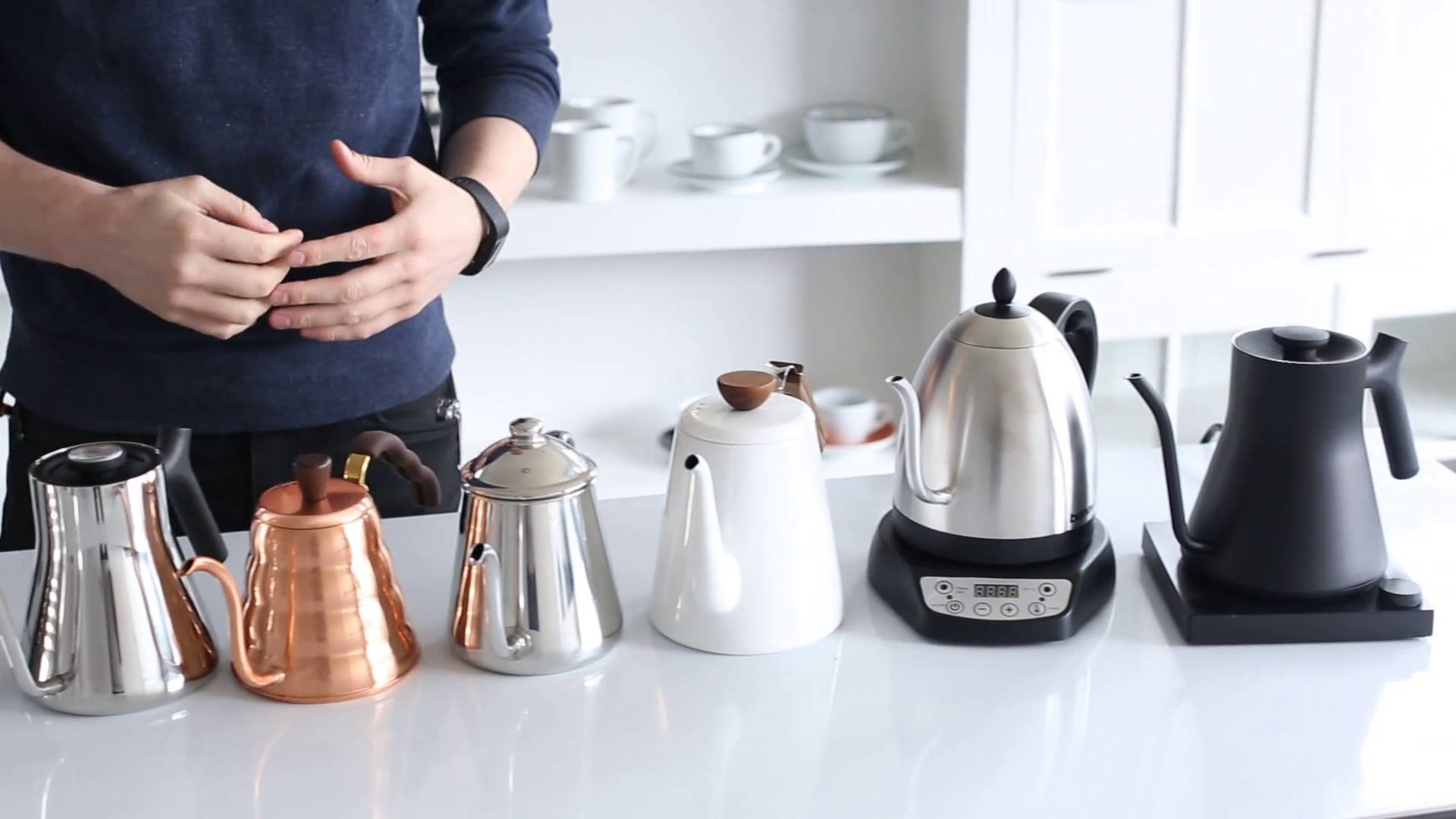 Six kettles on a counter