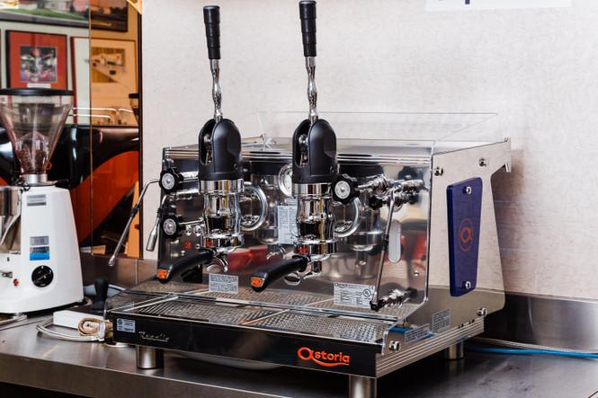 Astoria Rapallo AL lever espresso machine 2 group beside a white Mazzer Super Jolly espresso grinder.