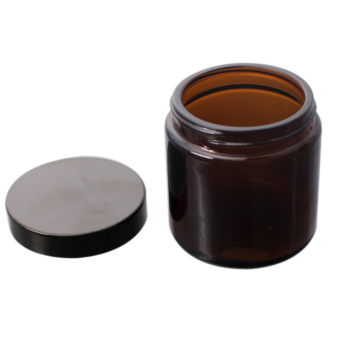 Included grounds jar and lid for the Comandante C 40 M K 3 hand grinder on a white background.