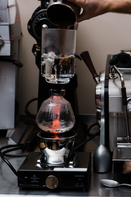 A user brewing coffee with the Cona glass filtering rod.