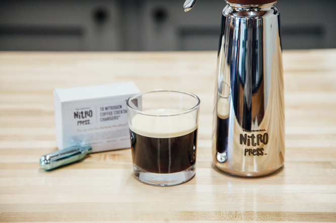 Box of Hatfields London Nitrogen Cartridges with one outside of the box next to a NitroPress and a nitro-infused cold brew in a glass.