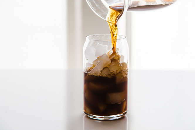 Pouring cold brew into a Libbey Can Shaped Glass with ice in it.