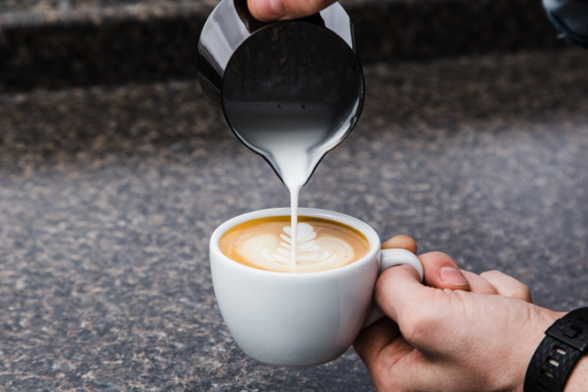 Pouring latte art with a Barista Hustle Precision Milk Pitcher into a Ancap mug.