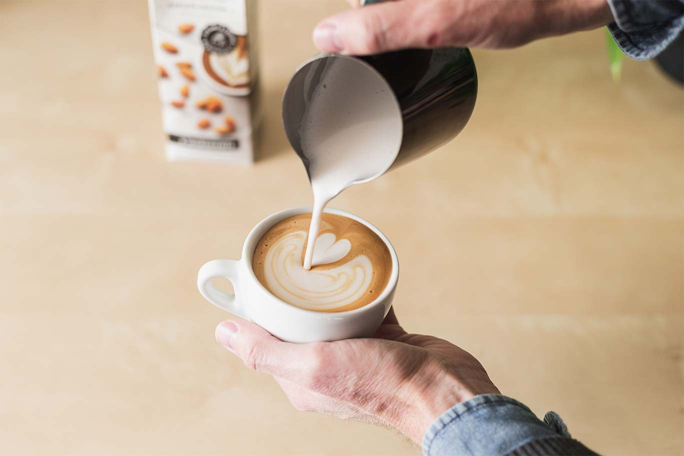 pouring steamed almond milk