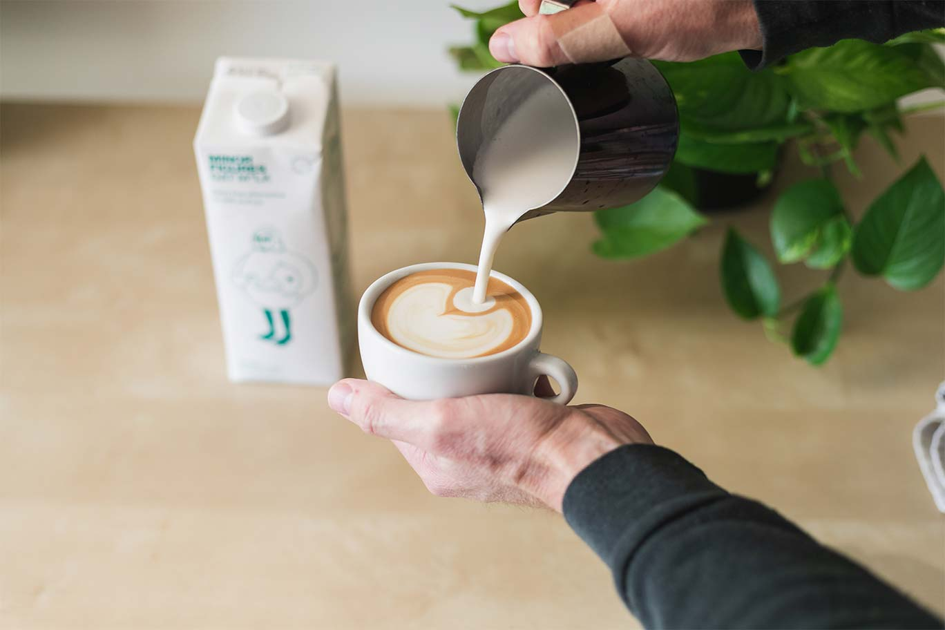 pouring steamed oat milk