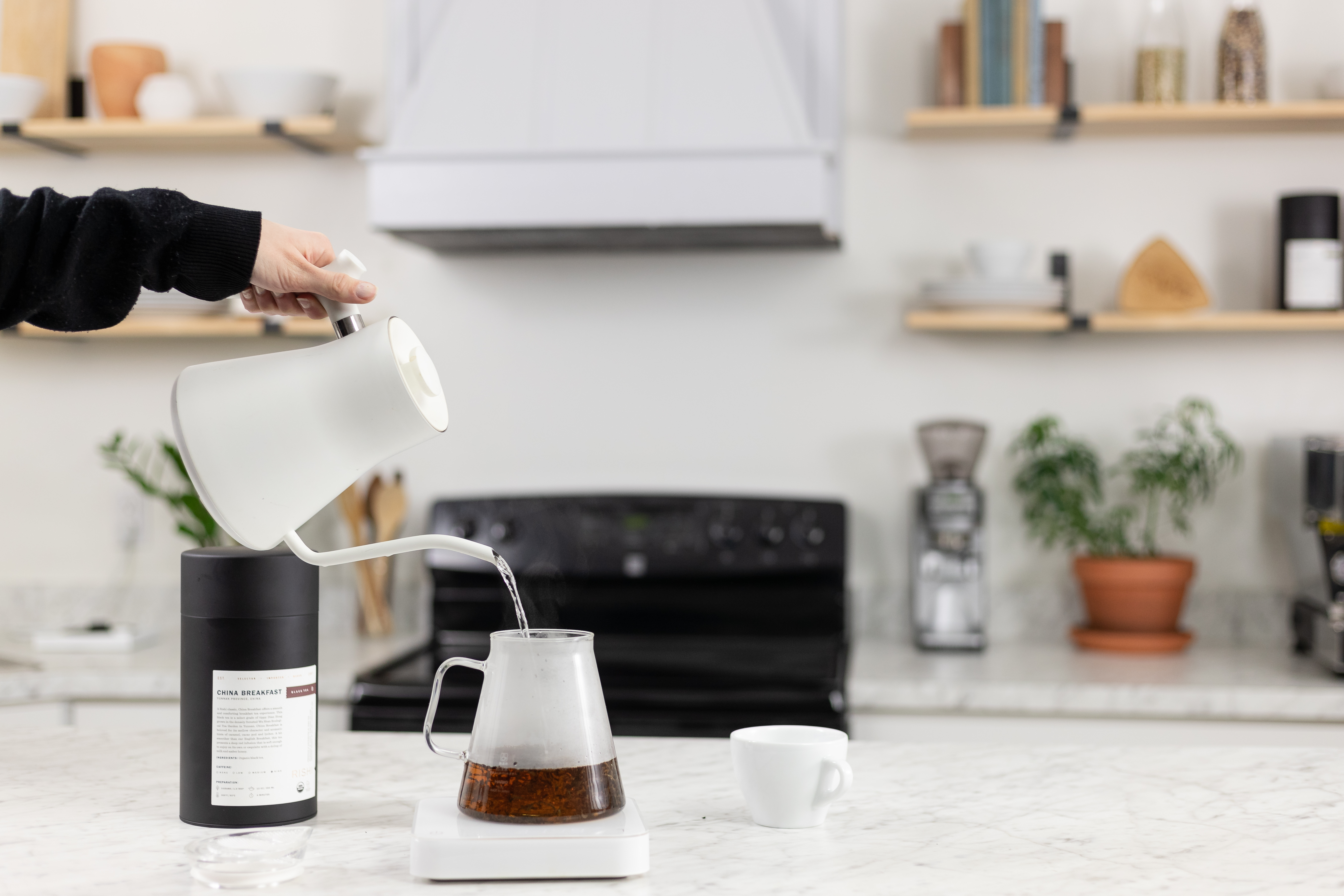 White Stagg EKG kettle pouring water into Hario Clear Teapot