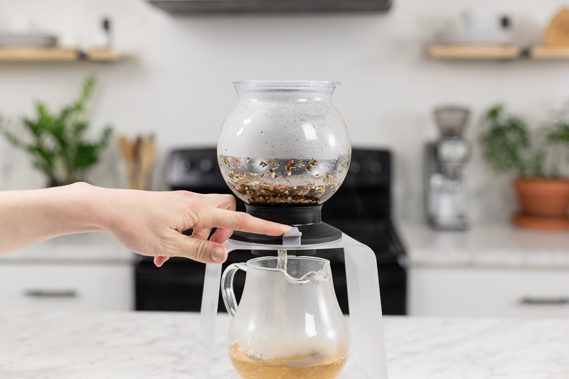 Finger Pressing the switch on the Hario Largo Tea Dripper