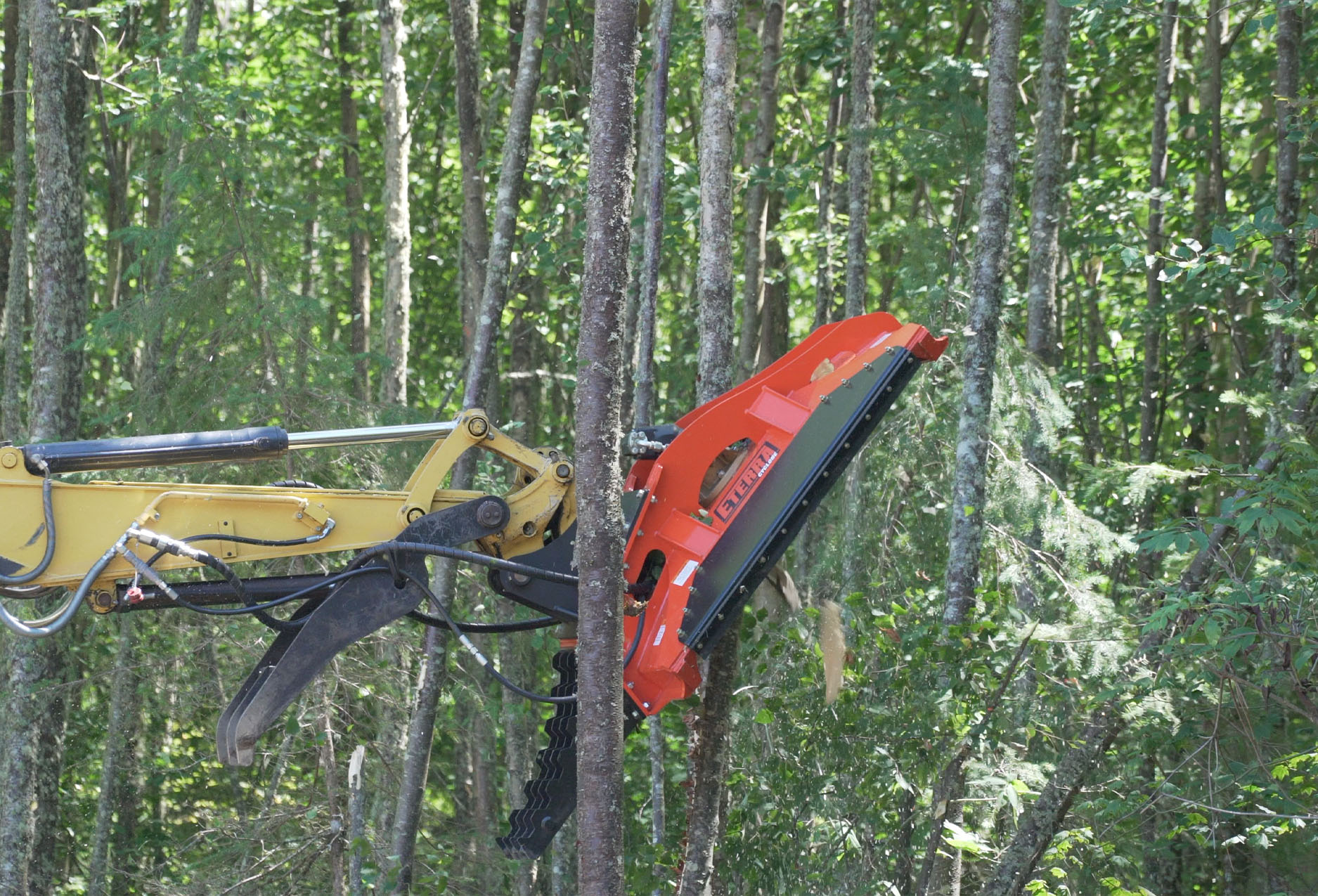 """side angle view of the cyclone 60"""" rotary brush mower attachment cutting down a tree."""