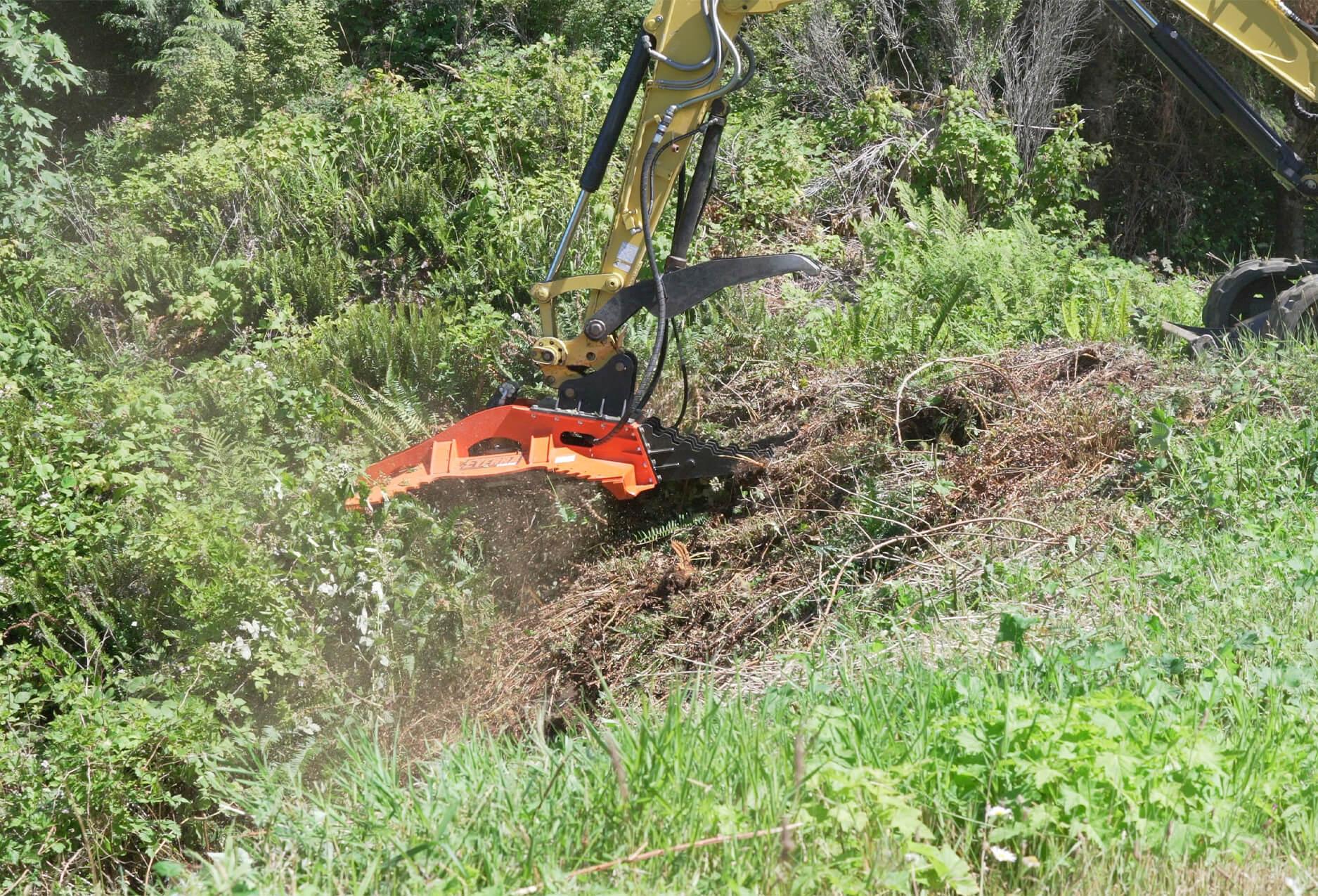 "The cyclone 60"" rotary brush mower clearing brush on a hillside."
