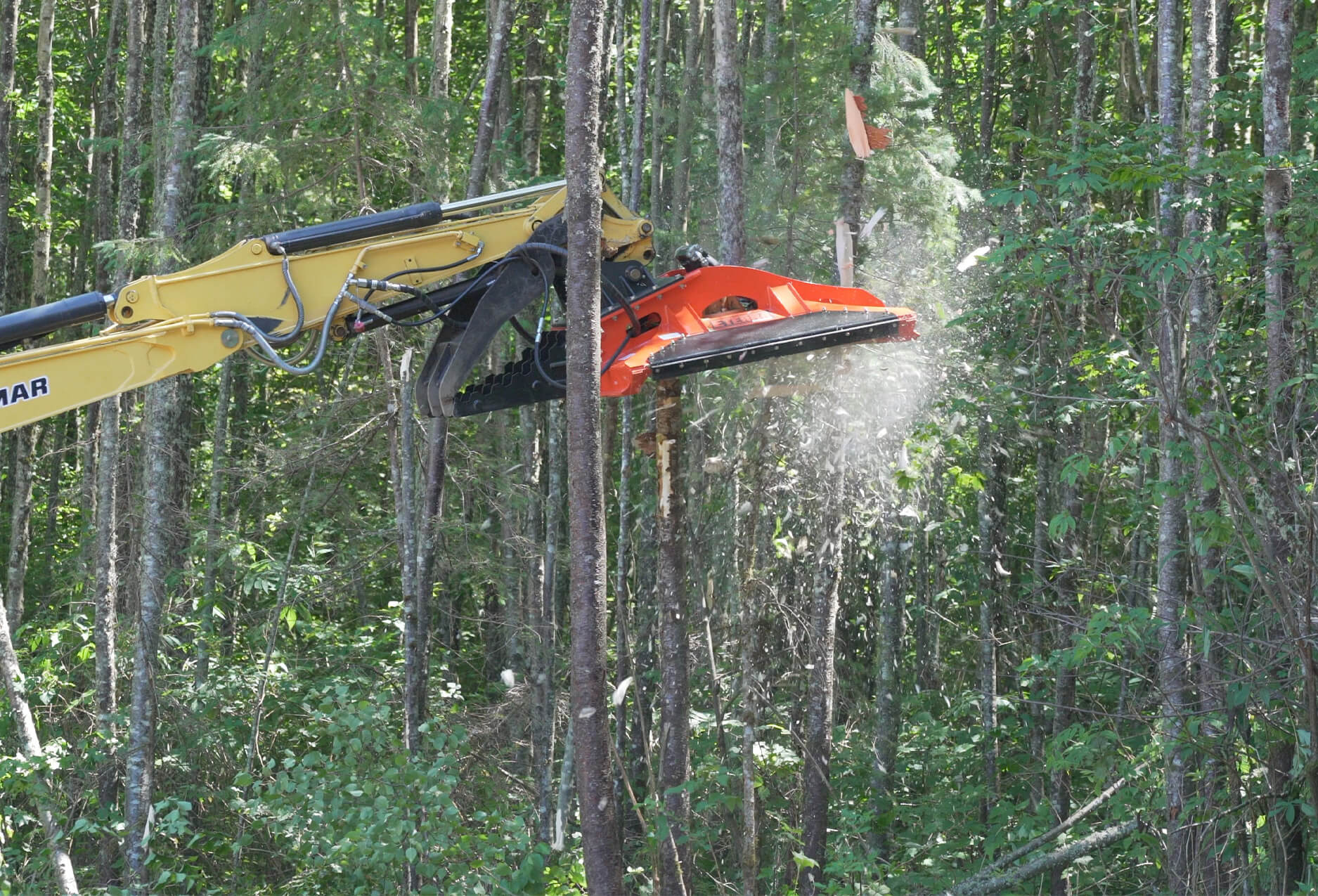 """action shot of the cyclone 60"""" rotary brush mower clearing a small tree."""