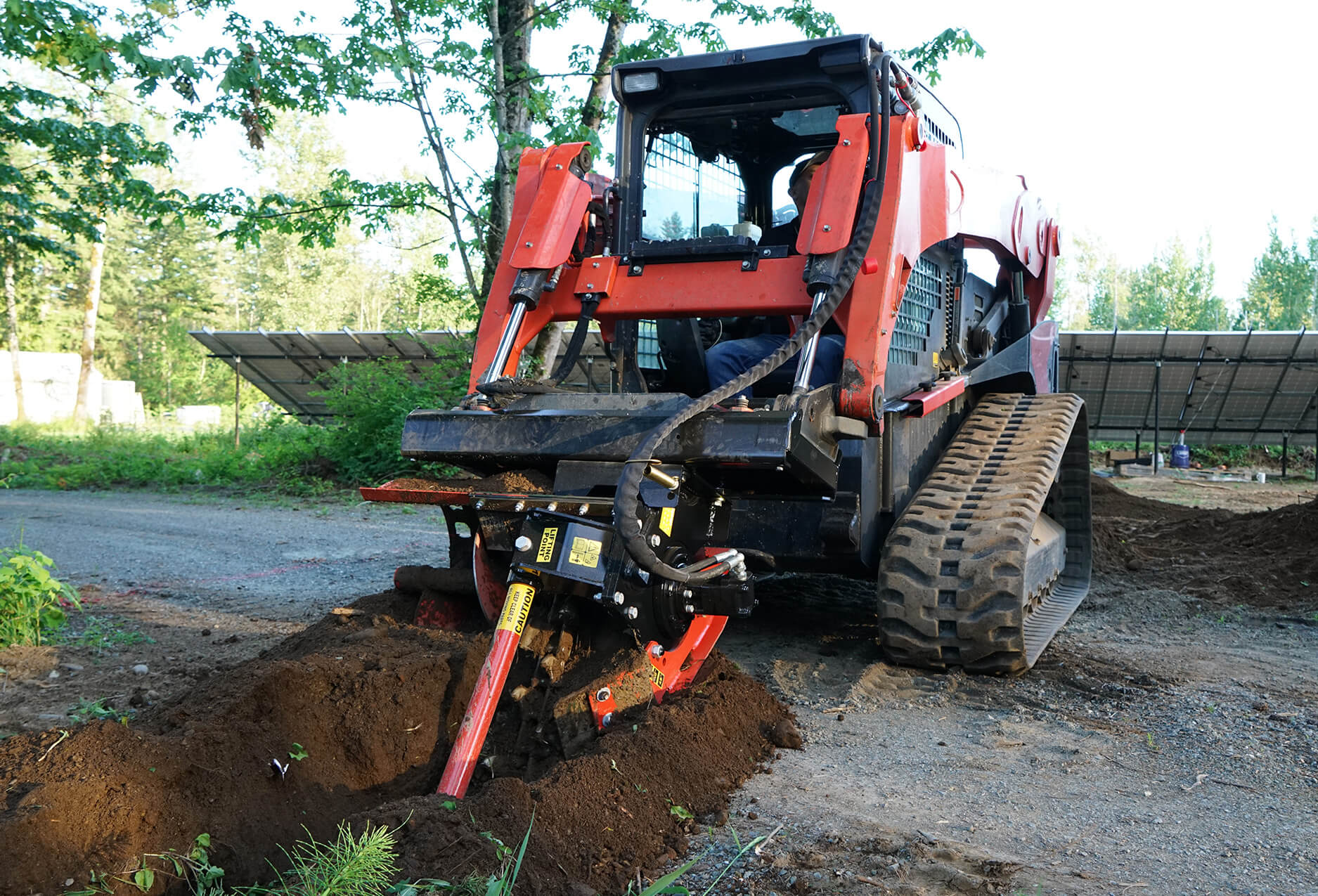 Constructing a water pipeline with the skid steer trencher attachment.