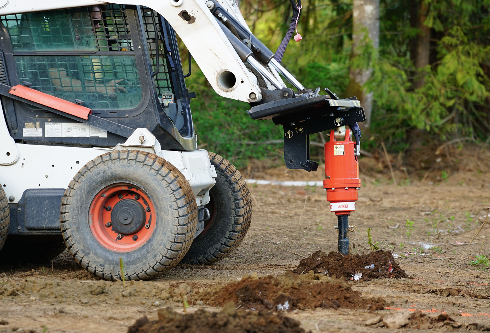 Skid Steer Auger drive Post Hole digging in soft earth conditions.