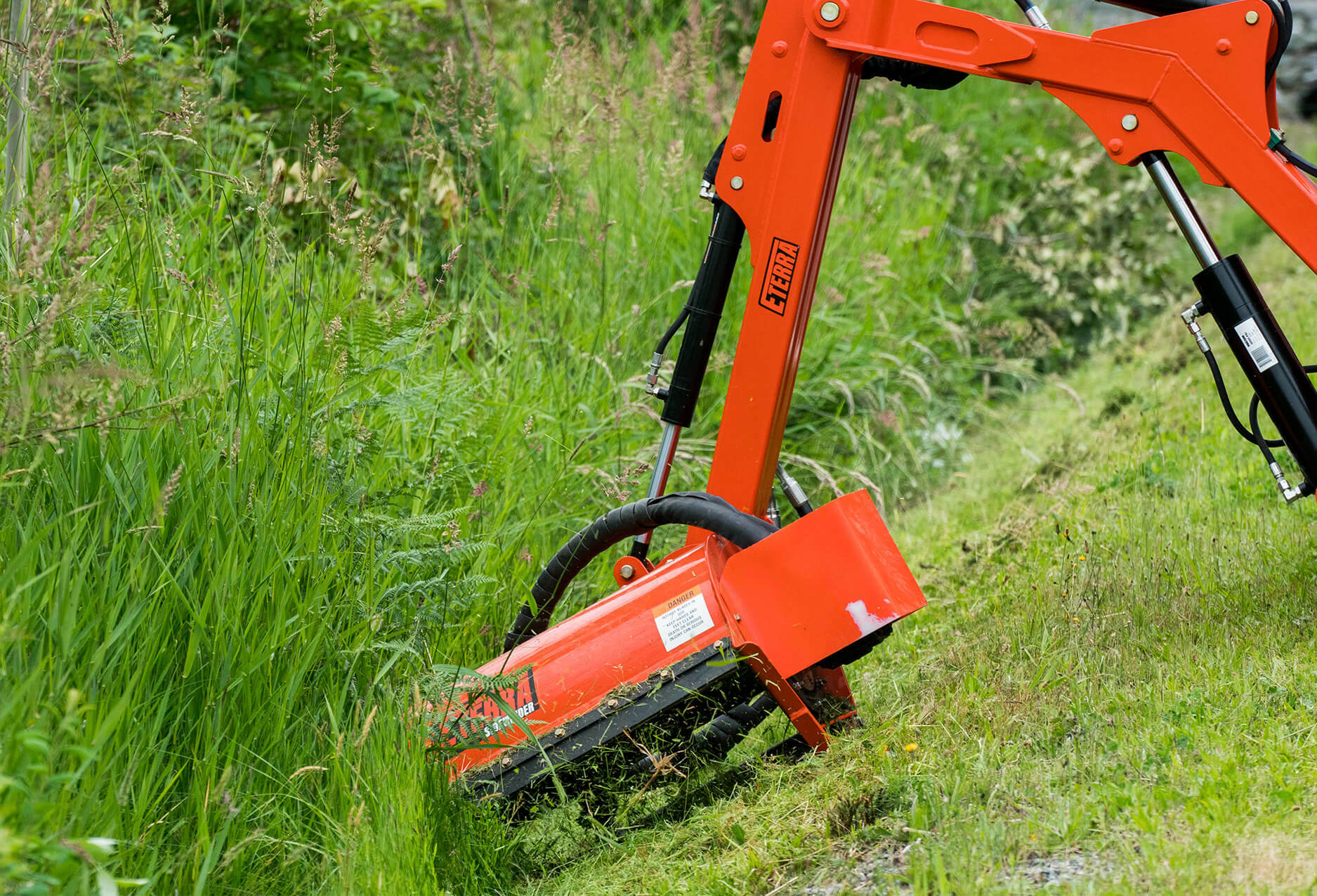 Eterra Sidewinder Skid Steer flail mower on Raptor boom arm mowing ditch closeup