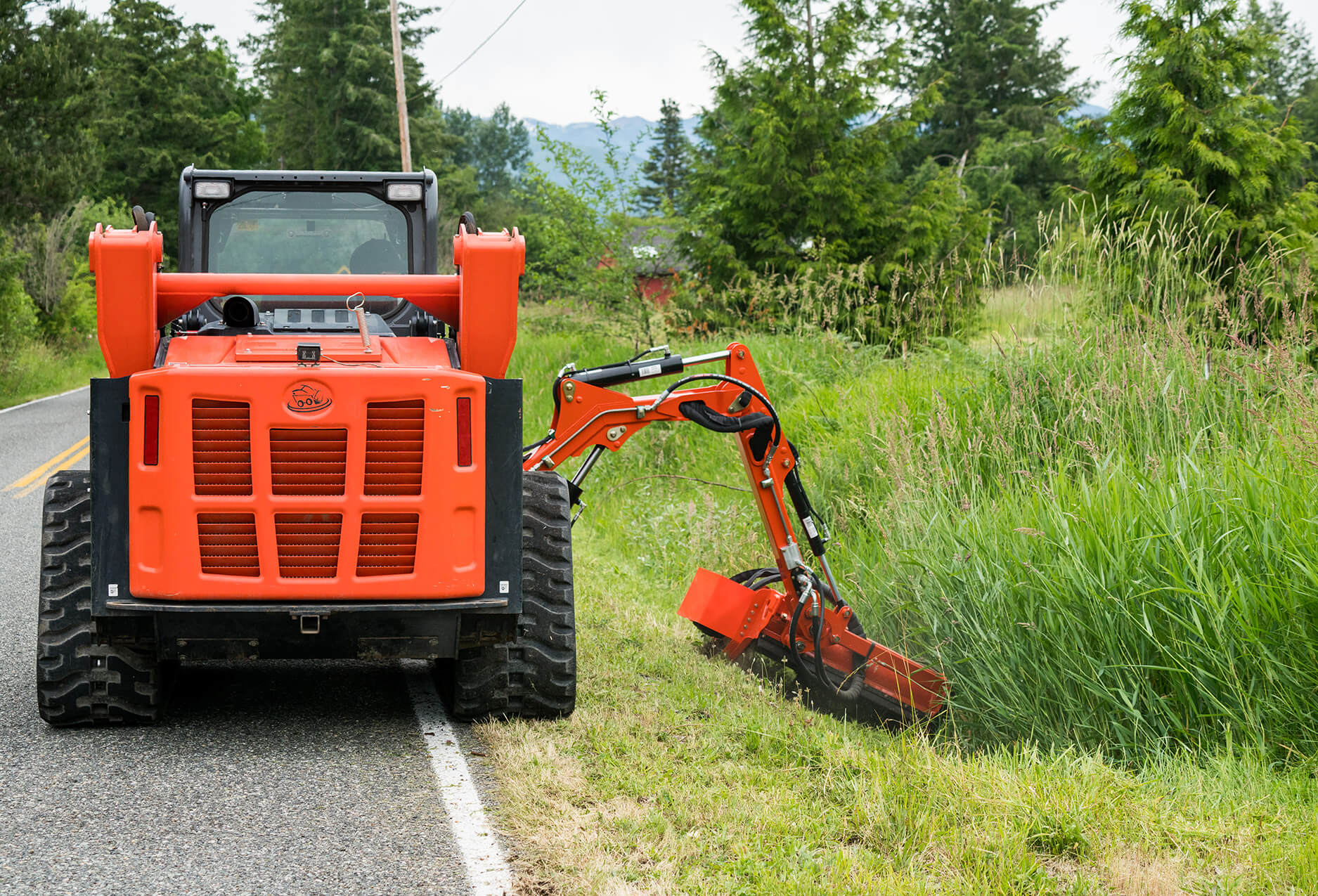 Eterra Sidewinder Skid Steer flail mower on Raptor boom arm mowing ditch back
