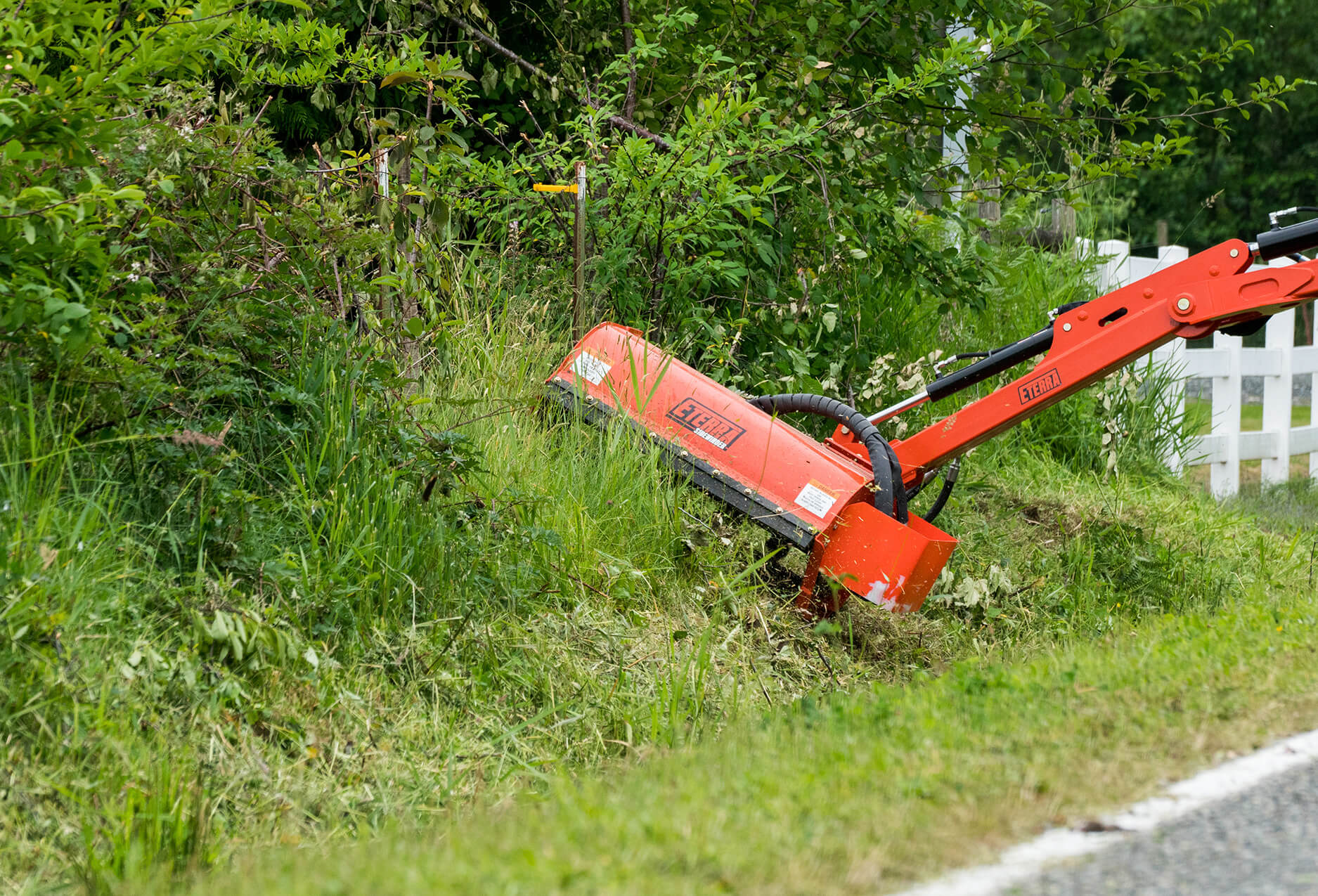 Eterra Sidewinder Skid Steer flail mower on Raptor boom arm mowing hillside