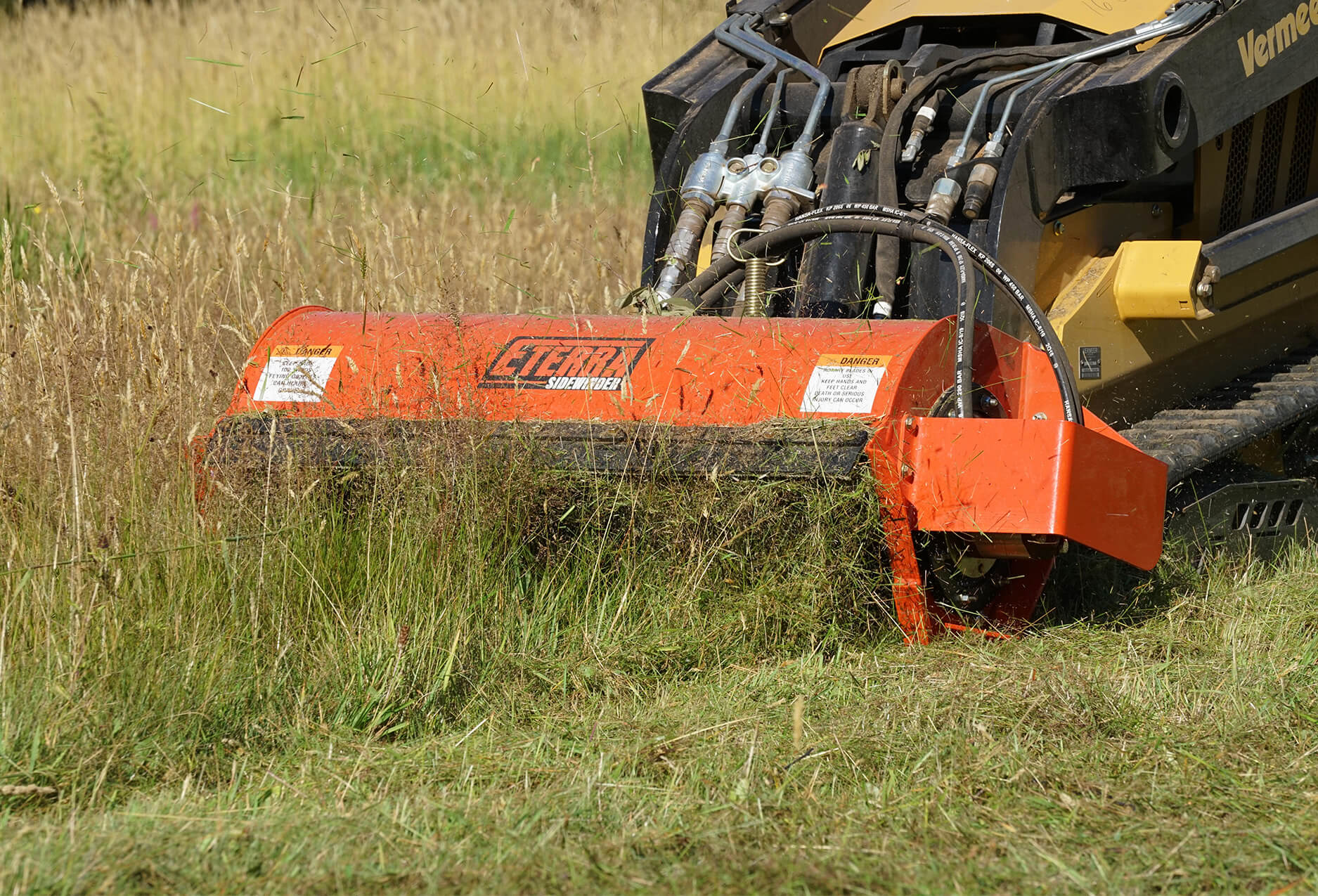 Eterra Sidewinder mini Skid Steer flail mower mowing grass close up